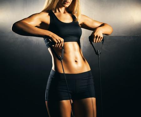 아름답고 건강한 스포티 한 소녀의 몸에 꼭 맞습니다. 슬림 여자 운동복에 포즈입니다.