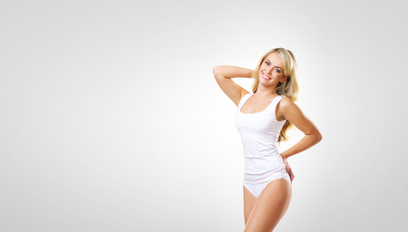 Young, beautiful and sporty woman in slimming underwear. Girl in white swimsuit. Stock Photo