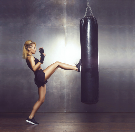 Fit and sporty young girl having a kickboxing training. Underground gym. Health, sport, fitness concept. Stock Photo
