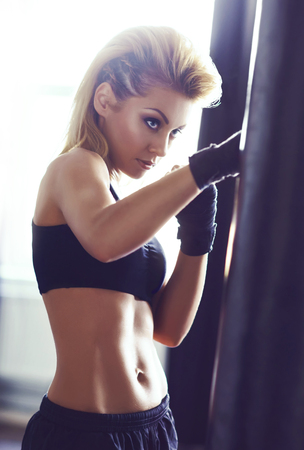 Fit and sporty young girl having a kickboxing training. Health, sport, fitness concept.