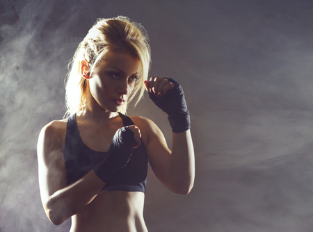 Fit and sporty young girl getting ready for a kickboxing training. Underground gym. Health, sport, fitness concept.