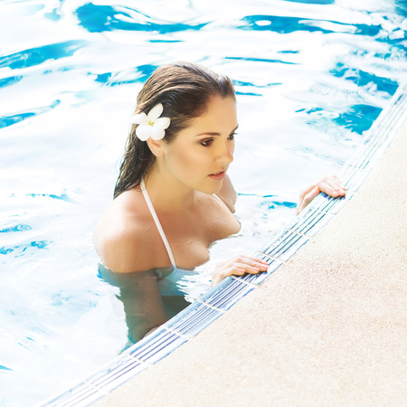 Young and sporty woman in swimsuit. Girl relaxing in a pool at summer. Stock Photo