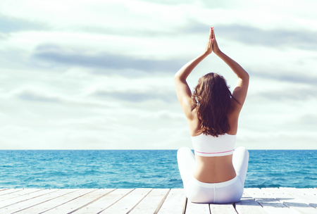 Attractive girl in white sporty clothes doing yoga on a wooden pier. Yoga, sport, leisure, recreation and freedom concept. Stock Photo