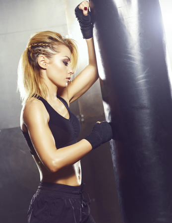 Fit and sporty young girl having a kickboxing training. Underground gym. Health, sport, fitness concept. Banco de Imagens