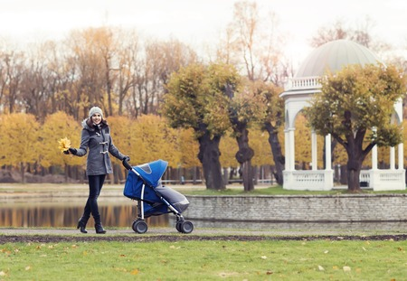 Mother playing in park with her toddler baby. Mom and son over seasonal autumn background.