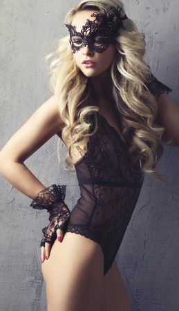 Young blond woman posing in sexy lingerie. Girl in mask and beautiful underwear.