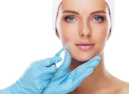 Beautiful face of the young woman and the medical scalpel in doctors hands isolated on white. Plastic surgery and face lifting concept.