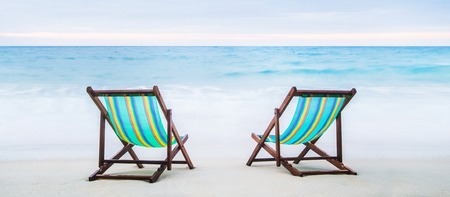 Lounge chairs on a tropical beach. Holidays and vacation concept. Stock Photo