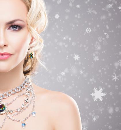 Mooie vrouw over de winterachtergrond met sneeuwvlokken. Kerstconcept.