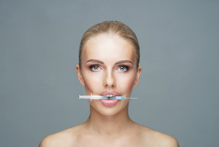 Doctor injecting in a beautiful face of a young woman. Plastic surgery concept. Imagens - 111575570