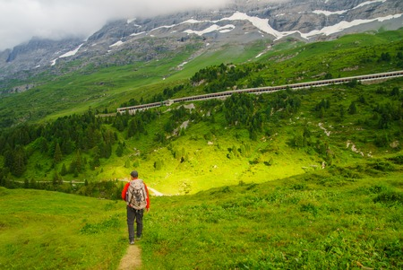 Hiker traveling in Alps. Alpine peaks landskape background. Jungfrau, Bernese highland. Sport, tourism and hiking concept. 免版税图像
