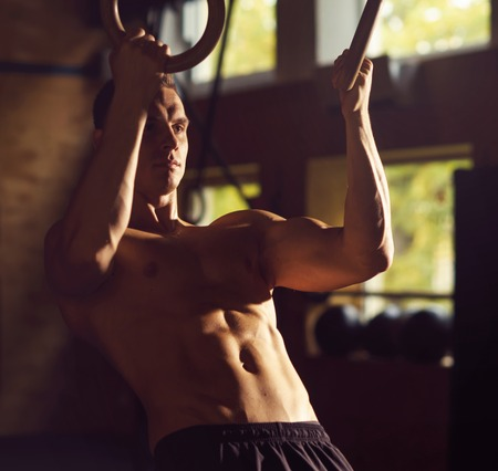 Fit, sporty and athletic sportsman working in a gym. Man training using gymnastic rings. Sports, athletics and fitness concept.