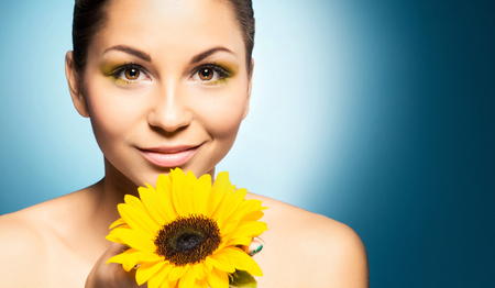 Portrait of beautiful woman and a sunflower over blue background. Spring concept.