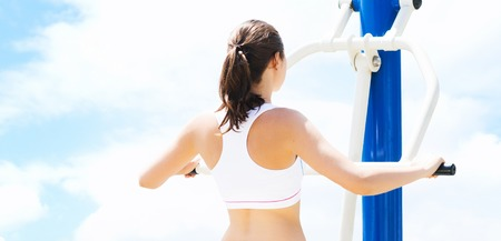 Sport and fitness concept. Young, fit and sporty woman working in a gym.