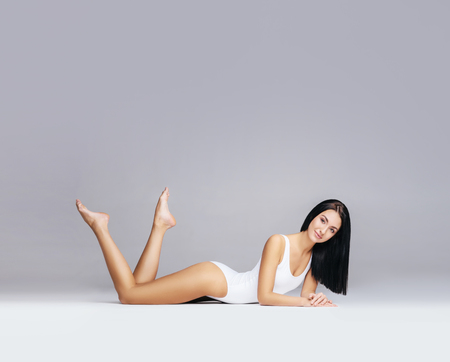 Beautiful fashion model in white swimsuit and hosiery. Young and beautiful woman posing in studio. Stock Photo