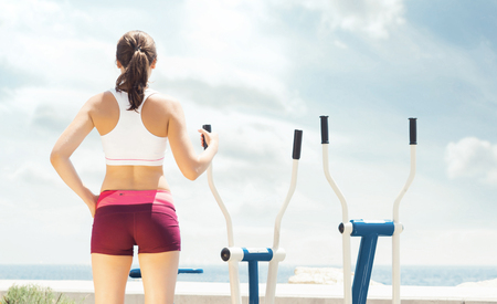 Young, fit and sporty girl training in outdoor gym. Fitness, sport and healthy lifestyle. Stock Photo