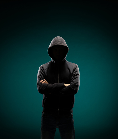 Computer hacker in hoodie. Obscured dark face. Data thief, internet fraud, darknet and cyber security concept. Imagens