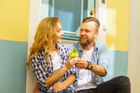 Man gives flowers to his girlfriend. Love, relations and dating concept. 免版税图像