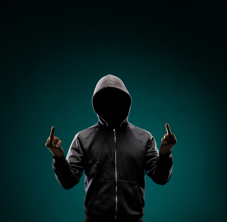 Computer hacker in hoodie. Obscured dark face. Data thief, internet fraud, darknet and cyber security concept. Stock fotó