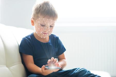 Ragazzino che utilizza l'autenticazione ID viso. Ragazzo con uno smartphone. Concetto di bambini nativi digitali. Archivio Fotografico