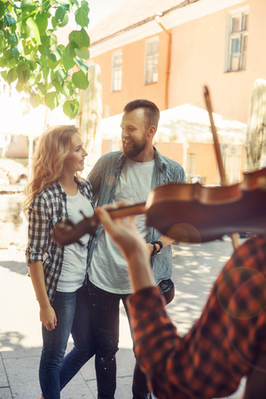 Young loving couple enjoying street musician with a violin