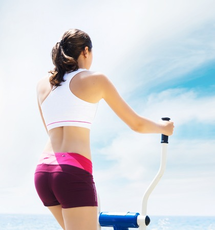 Young and sporty woman training in outdoor gym. Fitness, sport and health care. Stock Photo