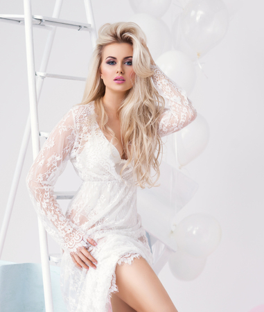 Young and beautiful blond girl in a white dress Stock Photo