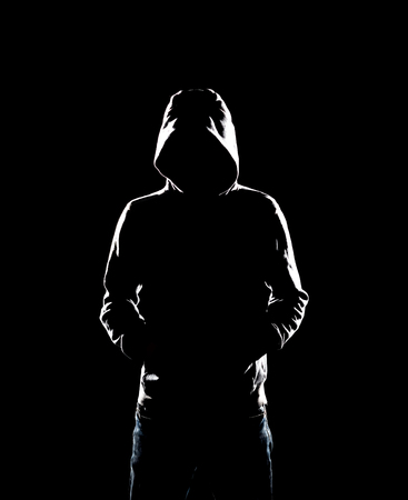 Portrait of computer hacker in hoodie. Obscured dark face. Data thief, internet fraud, darknet and cyber security concept.