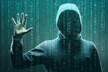 Hacker in maschera e felpa con cappuccio su sfondo binario astratto. Volto scuro oscurato. Ladro di dati, frode su Internet, darknet e sicurezza informatica.