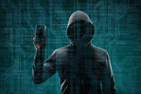 Dangerous hacker with a smartphone gadget over digital background with binary code. Obscured dark face in mask and hood. Data thief, internet attack, darknet fraud, virtual reality and cyber security.