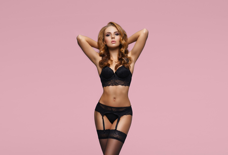 Young, sexy and beautiful fashion model posing in lingerie. Attractive blond girl in erotic underwear.