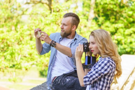 Man and woman taking photos with a camera and a smartphone. Imagens