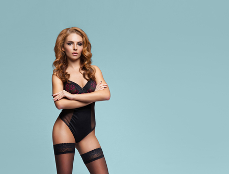 Young beautiful woman posing in sexy lingerie over colored background in studio. Girl in underwear.