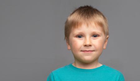 Portret szczęśliwy uśmiechający się chłopiec w niebieskiej koszulce. Atrakcyjny dzieciak w studiu.