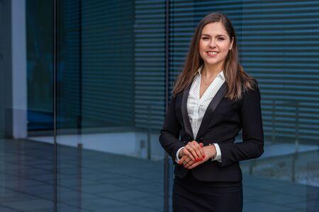 Selbstbewusste Geschäftsfrau vor modernem Bürogebäude. Geschäfts-, Bank-, Unternehmens- und Finanzmarktkonzept.