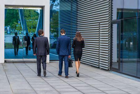 Przekonani biznesmeni rozmawiają przed nowoczesnym budynkiem biurowym. Biznesmeni i bizneswoman mają rozmowę biznesową. Koncepcja rynku bankowego i finansowego.