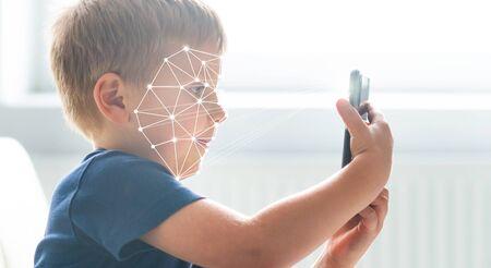 Kid using face id recognition. Boy with a smartphone gadget. Digital native children concept. Reklamní fotografie