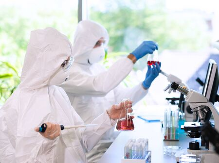 Scientifiques en combinaisons de protection et masques travaillant dans un laboratoire de recherche utilisant du matériel de laboratoire : microscopes, tubes à essai.