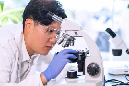 Asian scientist working in lab. Doctor making microbiology research. Laboratory tools: microscope, test tubes, equipment. Biotechnology, chemistry, bacteriology, virology, dna and health care.
