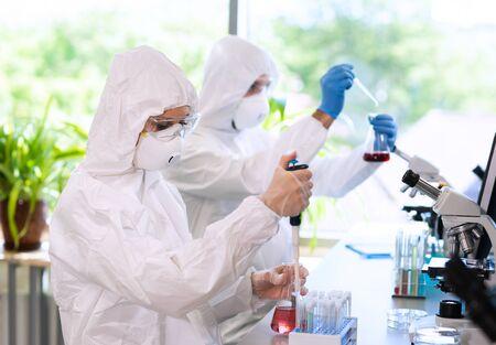Científicos en trajes de protección y máscaras que trabajan en el laboratorio de investigación utilizando equipos de laboratorio: microscopios, tubos de ensayo. Foto de archivo