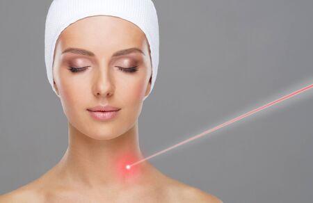 Doctor quitando lunares usando rayos láser. Retrato de belleza de una mujer joven. Eliminación de marcas de nacimiento, cirugía plástica, lifting de piel y medicina estética. Foto de archivo