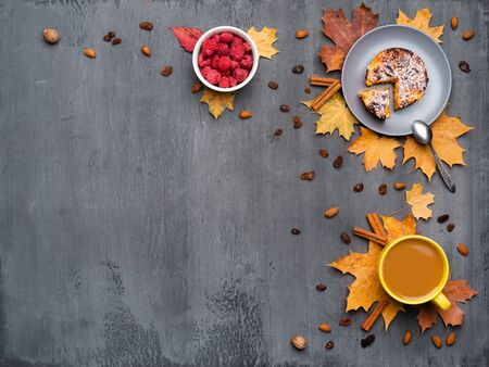 Seasonal autumn background. Frame of colorful maple leaves and a cup of hot drink, coffee, latte or cappuccino, nutmeg, cake, raspberries and cinnamon over grey. Imagens