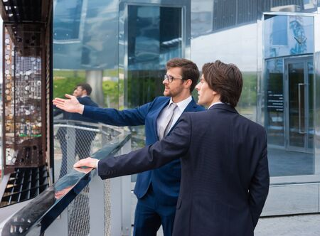 Confident business men talking in front of modern office building. Businessman and his colleague. Banking and financial market.