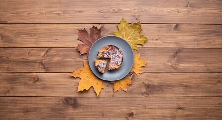 Seasonal autumn background. Frame of maple leaves and a cake over wooden background.