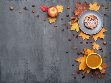 Seasonal autumn background. Frame of colorful maple leaves and a cup of hot drink, coffee, latte or cappuccino, nutmeg, cake, apple and cinnamon over grey. Banco de Imagens