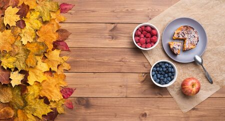 Seasonal autumn background. Frame of maple leaves and a cake and berries over wooden background. Imagens
