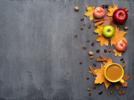 Seasonal autumn background. Frame of colorful maple leaves, peaches and apples over grey