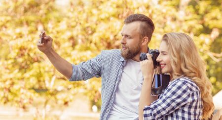 Man and woman taking photos with a camera and a smartphone in autumn park.