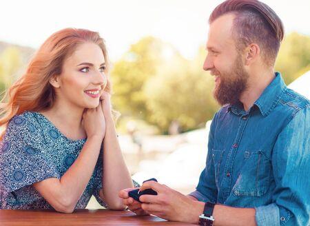 Sposami concetto. Coppia di innamorati fidanzarsi in un caffè all'aperto. Sfondo autunnale.