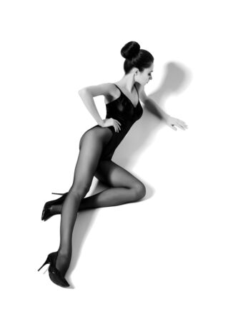 Beautiful fashion model in black swimsuit and hosiery. Young and beautiful woman posing in studio. Imagens